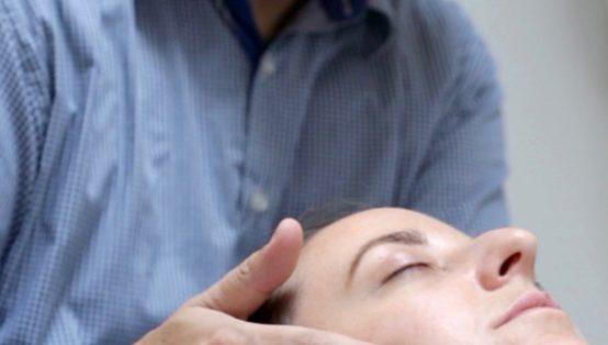 Healer holder hænder om kvindes hoved